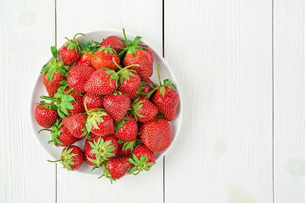 흰색 배경에 접시에 익은 딸기. 상위 뷰, 복사 공간입니다.