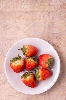 テキストのビンテージ紙の背景の場所に丸い白いプレートで熟したイチゴ