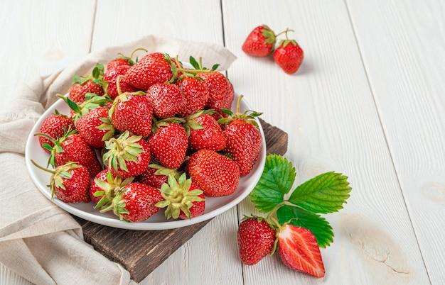 밝은 배경에 하얀 접시에 익은 딸기. 상위 뷰, 복사 공간입니다.