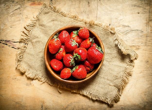 袋のボウルに熟したイチゴ。木製のテーブルの上。