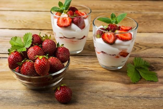 Ripe strawberries and layered cream cheese dessert on wooden
