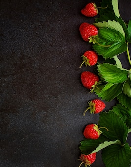 Ripe strawberries and leaves on black background. top view