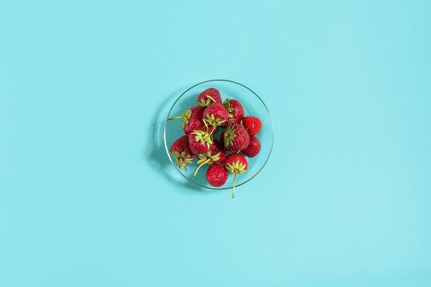 Спелая клубника на блюдце, изолированном на фоне мяты. вид сверху. скопируйте пространство. плоский макет натюрморта