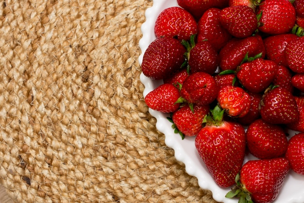 Ripe strawberries on white plate  on jute tablecloth