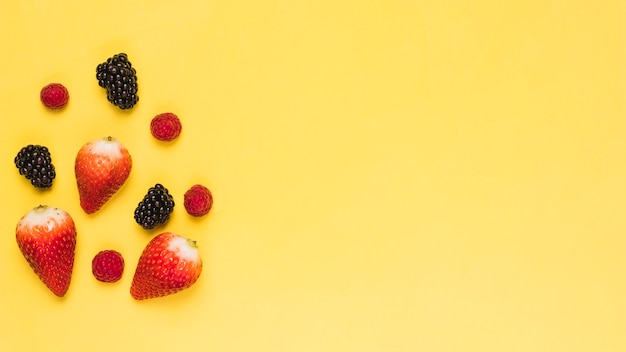 Ripe strawberry blackberry and raspberry on yellow background