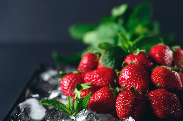 Ripe strawberry on ice with mint leaf