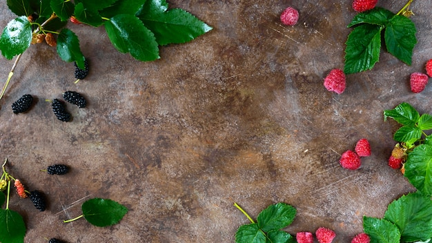 。熟した夏の果実。ビンテージ背景にラズベリー、桑、緑の濡れた葉。プロジェクト用の空き容量。バナー。