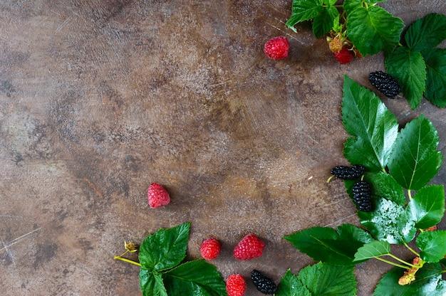 。熟した夏の果実。ビンテージ背景にラズベリー、桑、緑の濡れた葉。プロジェクト用の空き容量