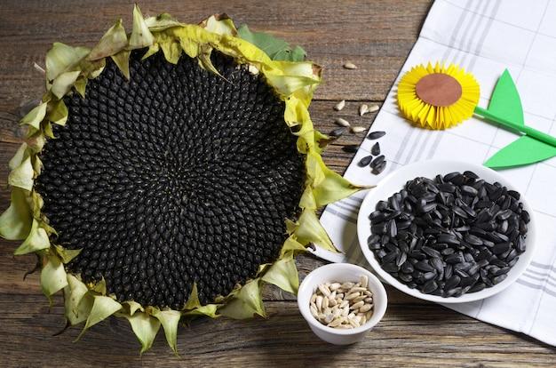 古い木製のテーブルの上に皮をむいた、皮をむいていない種子と熟したヒマワリ