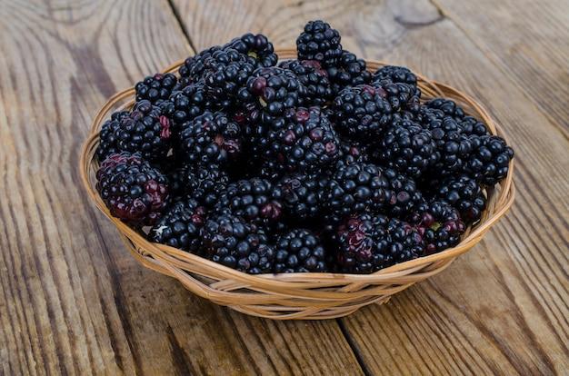 木製のボウルに熟した甘い黒いブラックベリー。