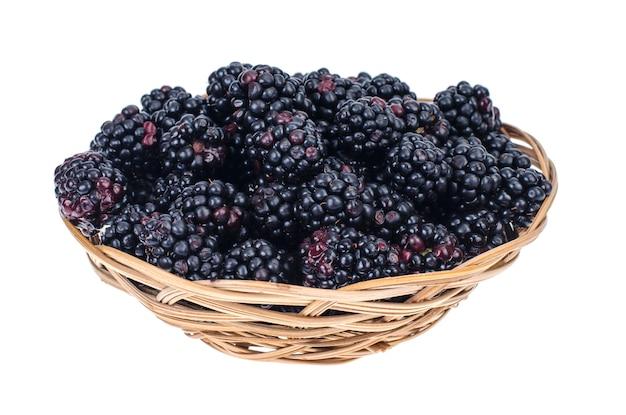 Ripe sweet black blackberries in wooden bowl.