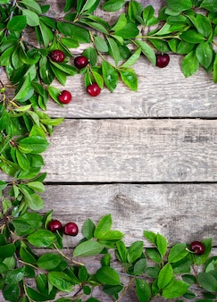 熟した甘いチェリーと木製のテーブルの緑の葉