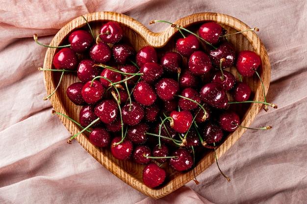 분홍색 배경 위에 있는 하트 모양의 나무 접시에 익은 달콤한 체리
