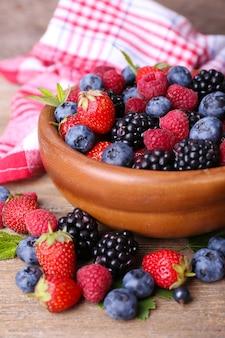 오래 된 나무 테이블에 그릇에 익은 달콤한 다른 열매