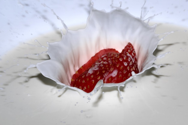 Ripe sweet fresh strawberry in cream with splashes and bubbles close-up