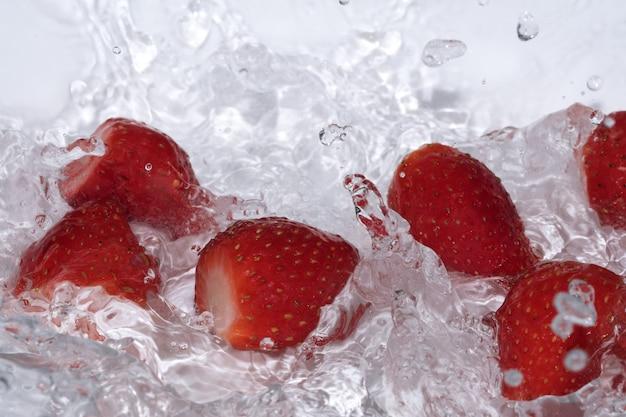 熟した甘い新鮮なイチゴは、水しぶきと泡のクローズアップできれいな冷水で洗われます