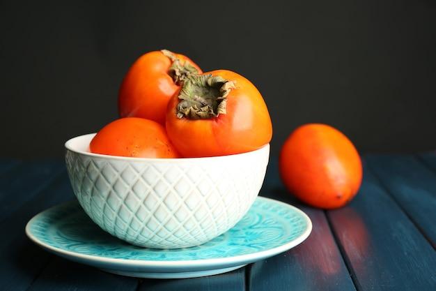 木製のテーブルの上に、熟した甘い柿