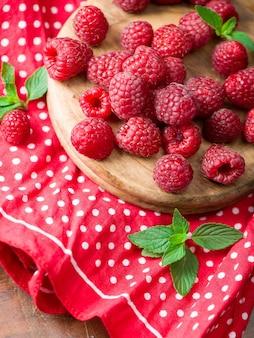 Спелые сладкие малины в шаре на деревянном столе. крупным планом, вид сверху, продукт с высоким разрешением