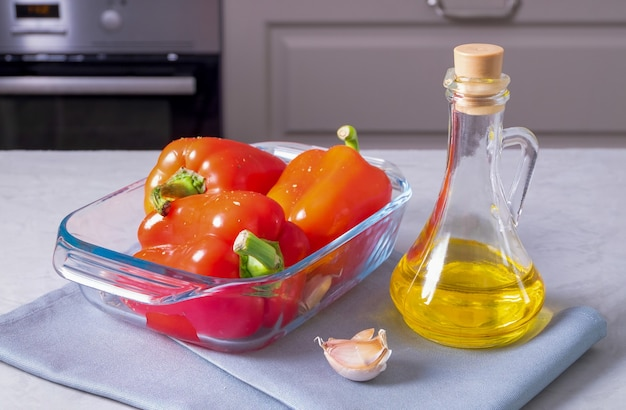 잘 익은 달콤한 고추는 올리브 오일, 마늘 및 말린 허브와 함께 오븐에서 구울 수 있도록 준비됩니다.