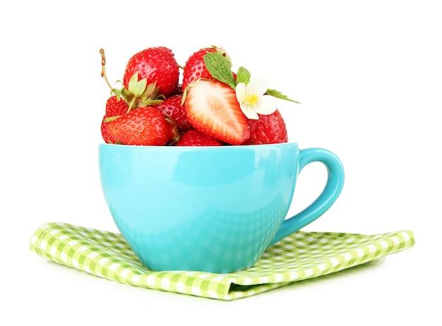 白で隔離される青いカップの熟した甘いイチゴ