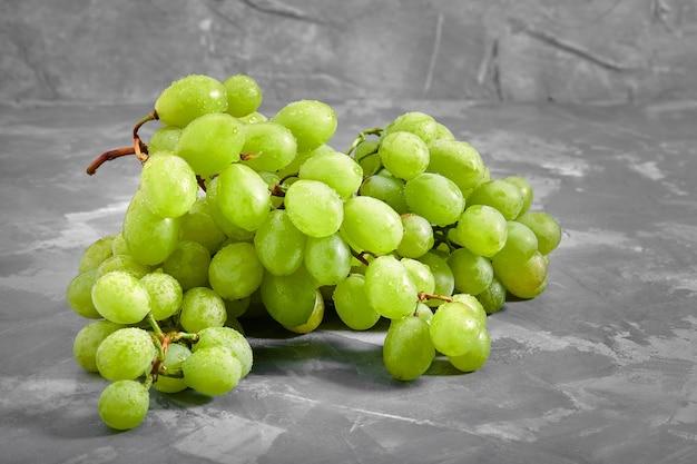 熟した甘い白ブドウ。ブドウの房とコンクリートの灰色の背景にブドウ。