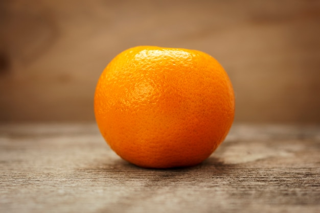 Ripe tangerine on a wooden table on a brown background