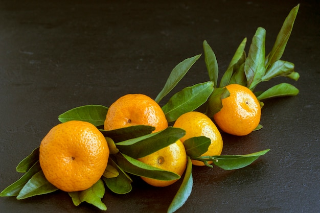 Ripe tangerines on a black background.