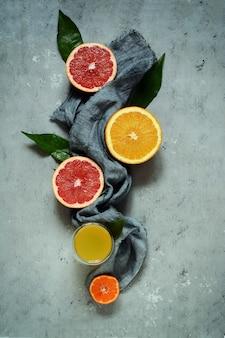 灰色の背景に熟したみかん。フルーツのレイアウト。柑橘類。