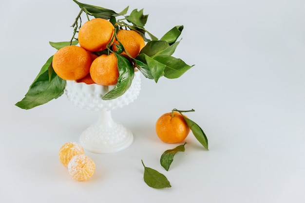 Ripe tangerines with green leaf on white background.