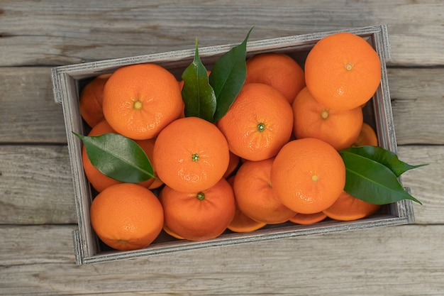 Ripe tangerines with green leaves in a wooden box on wooden