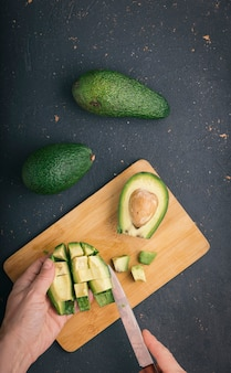 Ripe and tasty avocado fruits on a cutting board with a knife