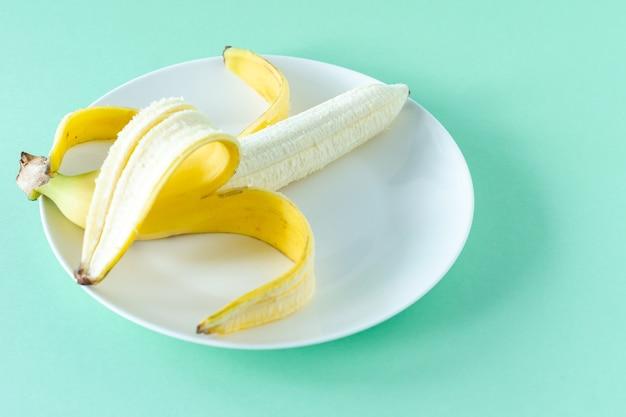青い背景のプレートに熟したおいしいバナナ。健康的な食事の概念。