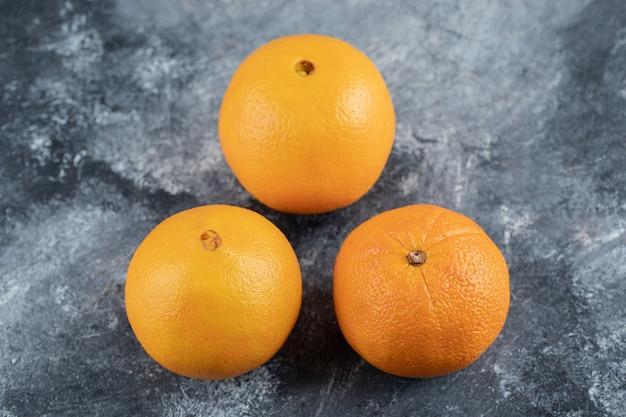 Спелые вкусные апельсины на мраморном столе.