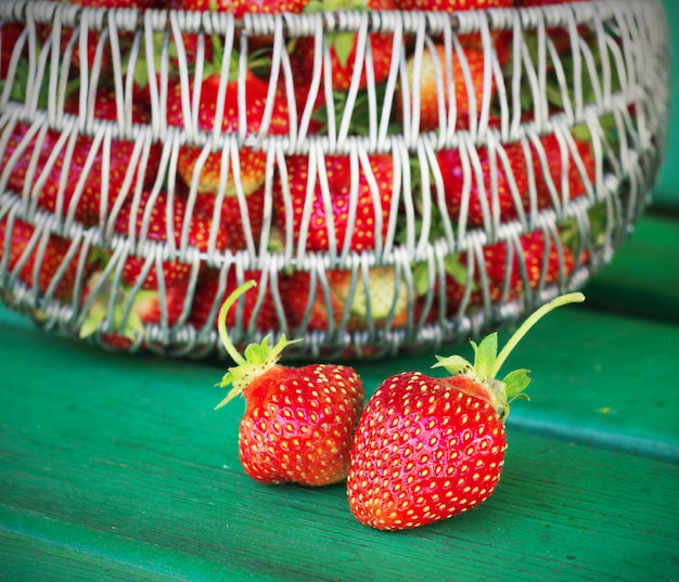 Ripe and tasty strawberries metal a basket in the street on  green bench