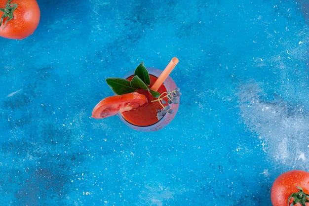 完熟トマトとトマトジュースのボード、青い背景。高品質の写真