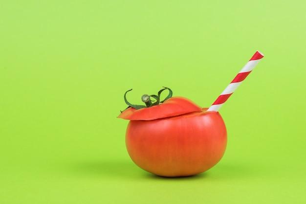 緑の背景に赤いカクテルチューブと完熟トマト。