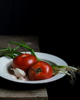 熟したトマトと古い木製のテーブルにねぎ。