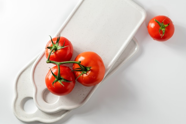 Ripe tomatoes on a branch, ceramic boards for serving, white background, top view