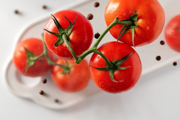 Ripe tomatoes on a branch, white background, top view, close-up