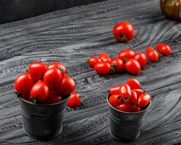 Ripe tomatoes in mini buckets on grey wooden and black wall, high angle view.