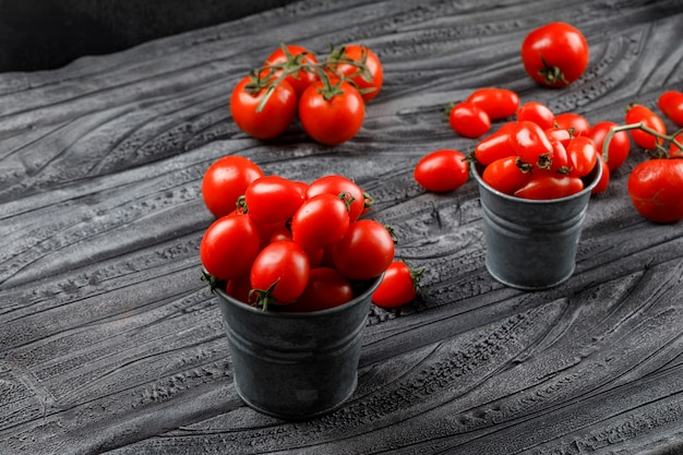 Ripe tomatoes in mini buckets on grey wooden and black wall. high angle view.