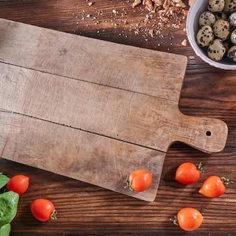 잘 익은 토마토, 메 추 라 기 계란 그릇 및 빈 보드 및 복사 공간 발가락 나무 보드에 너트 부스러기. 샐러드 준비 개념. 평면도