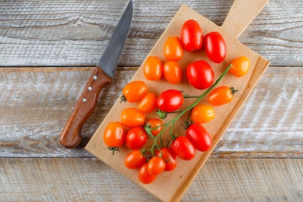 木製とまな板の上に平らなナイフで熟したトマトを置く