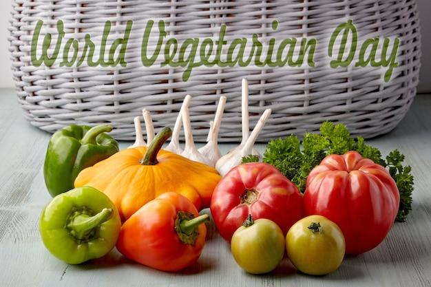 Спелые овощи и зелень из сада на деревянном синем столе на фоне корзины. надпись всемирный день вегетарианцев