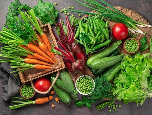 Спелые овощи и зелень в большом ассортименте на коричневом фоне. вид сверху. здоровая, здоровая еда.