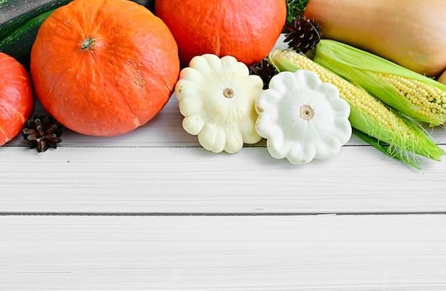 白い背景の上の秋の庭から熟した野菜のトウモロコシとカボチャ秋の秋のコンセプト