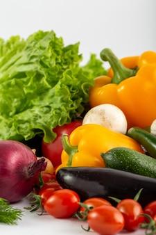 熟した野菜の白い背景の上の新鮮なカラフルなサラダ野菜