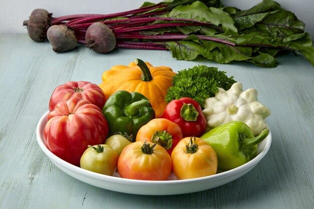 На белой тарелке выкладываются спелые овощи с грядки