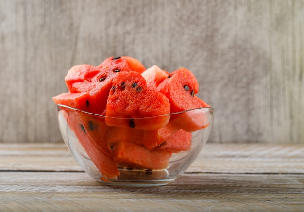 Ripe watermelon pieces in a glass bowl on wooden and grunge background. side view.