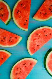 Ripe watermelon slices on a blue background. top view. vertical.